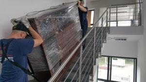 Robotnicy wnoszą po schodach meble, transport mebli